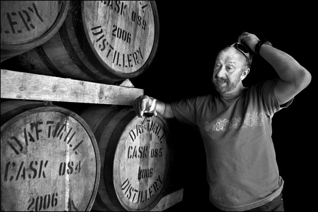 Un spécialiste juif de whisky posé sur un tonneau dans une distillerie de Fife. (Crédit : Judah Passow)