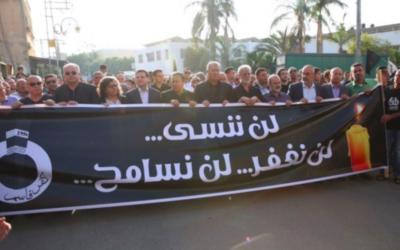 """Des membre de la Liste Arabe Unie se rassemblent à Kafr Kassem pour commémorer le soixantième anniversaire du massacre commis par la Police des Frontières israélienne dans le village. Sur la bannière, on peut lire : """"Nous n'oublierons pas ni ne pardonnerons"""" (Crédit : Porte-parole de la Liste Arabe Unie)"""