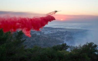 Des avions de lutte contre le feu israéliens essaient d'éteindre un incendie qui fait rage dans la ville de Haïfa, au nord du pays, où un grand incendie a fait rage dans la ville le 24 novembre 2016. (Crédit : Yaakov Cohen/Flash90)