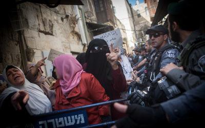 Des musulmanes palestiniennes de l'organisation Murabitun crient des slogans, le Coran à la main, pendant une manifestation contre les policiers israéliens qui les empêchent d'entrer au complexe du mont du Temple de la Vieille Ville de Jérusalem, le 17 septembre 2015. (Crédit : Miriam Alster/Flash90)