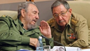 Le président cubain Fidel Castro, président Cubain de l'époque (à gauche) aux côtés de son frère Raul, Ministre des Forces Armées Révolutionnaires, en pleine discussion à la Havane au cours de la dernière réunion du Parlement cubain le 23 décembre 2003. (Crédit :  AFP PHOTO/ADALBERTO ROQUE)