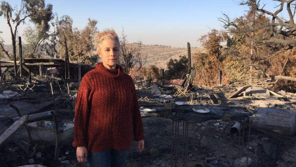 Rama Ben Zvi devant les restes carbonisés de son restaurant campagnard célèbre, le Rama's Kitchen, dans le village de Nataf, le 27 septembre 2016. (Crédit : Jessica Steinberg/Times of Israel)
