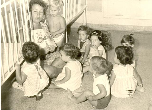 Des enfants et leur nurse dans la Maison des Enfants dans le Kibboutz Afikim au milieu des années 1960. (Crédit : Kibbutz Afikim Archive via wikipedia)