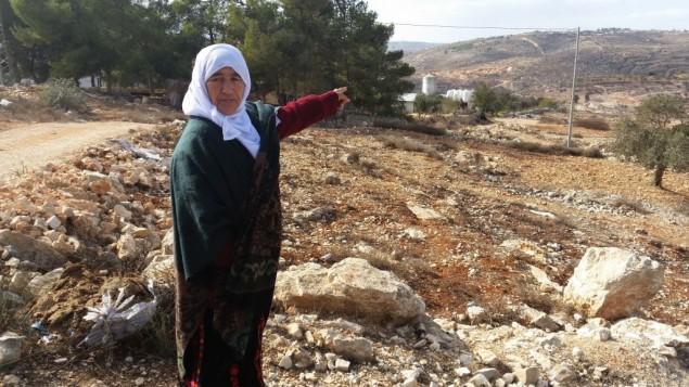 Une Palestinienne désigne la terre qui appartenait selon elle à sa famille avant qu'Israël n'établisse l'avant-poste d'Amona, en Cisjordanie, en 1996. Novembre 2016.  (Crédit : Raphael Ahren/Times of Israel)