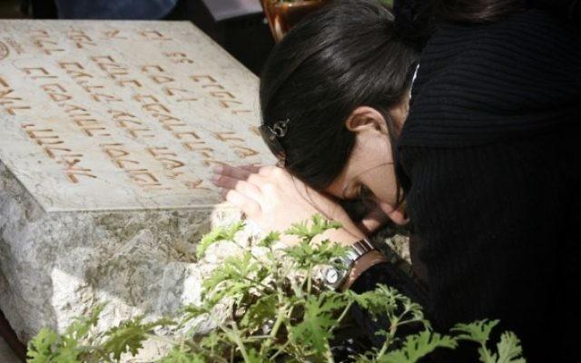 Une femme pleure sur une tombe lors d'une cérémonie organisée à la mémoire des soldats tombés au combat lors de la crise de Suez, le 8 novembre 2007. (Crédit : Michal Fattal/Flash90)