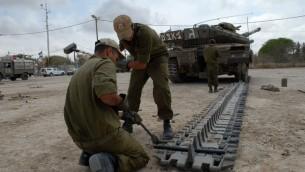 Des soldats réparent la chenille d'un tank stationné à proximité du Kibboutz Kissufim, près de la Bande de Gaza en 2012. (Crédit : Almog Sugavker/Flash90)
