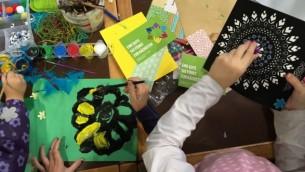 """Des objets d'art et d'artisanat durant la Journée de la  Mitzvah au foyer pour réfugiés de Spandau. L'une des cartes affiche : """"Une bonne action mène à l'autre"""".  13 Novembre  2016. (Courtesy)"""