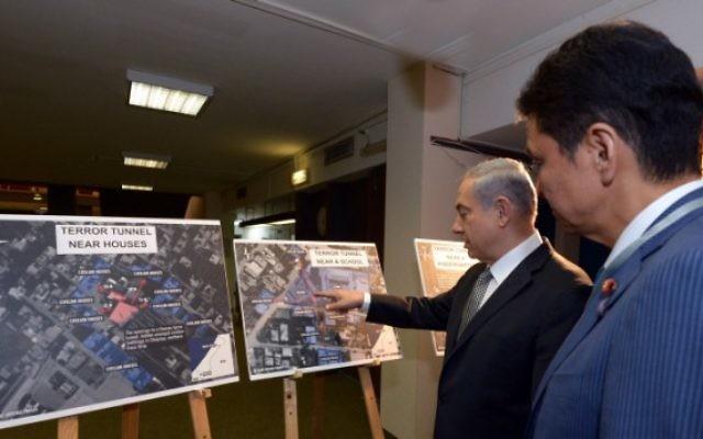 Le Premier ministre Benjamin Netanyahu montre au ministre des Affaires étrangères du Japon des cartes retraçant la présence des tunnels terroristes de Gaza en Israël, au cours de sa visite dans le pays le 24 juillet 2014. (Crédit : Haim Zach/GPO)