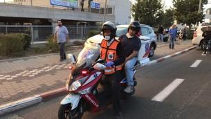 Le ministre de l'Education Naftali Bennett sur le siège arrière d'un scooter-ambulance de la flotte de United Hatzalah pour évaluer la situation à Haifa, le 24 novembre 2016, alors que feu fait rage autour de la ville. (Crédit : United Hatzalah)