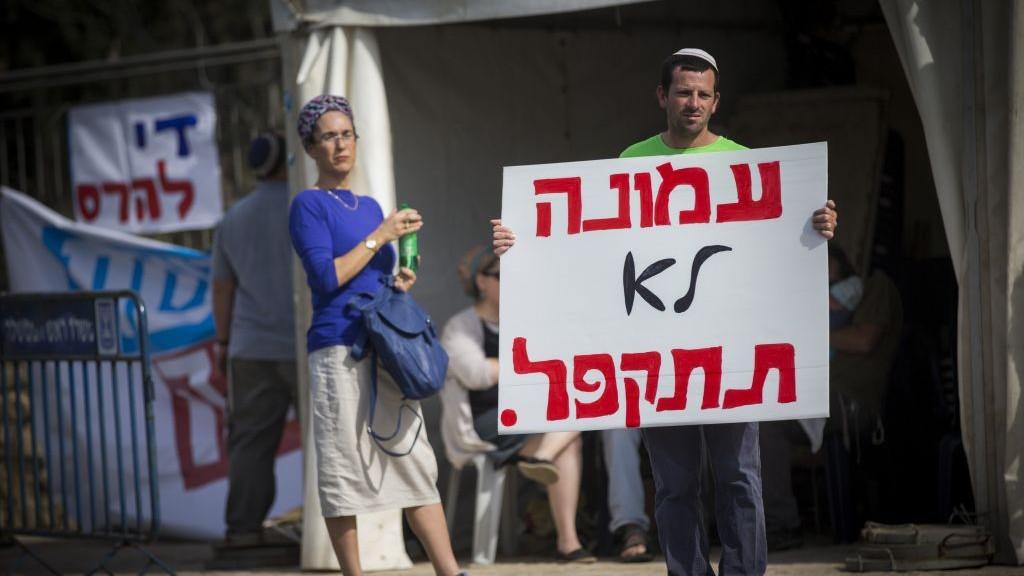 Les Israéliens des implantations juives en Cisjordanie d'Ofra et Amona manifestent pour demander l'approbation d'une loi légalisant les avant-postes en Cisjordanie, aux abords du bureau du Premier ministre à Jérusalem, le 13 novembre  2016. (Crédit : Yonatan Sindel/Flash90)