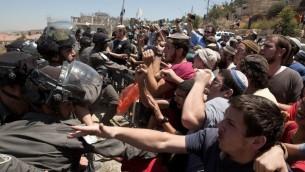Les résidens israéliens affrontent les forces de sécurité alors que les démolitions commencent dans l'implantation Beit El, en Cisjordanie, le 29 juillet 2015. (Crédit : AFP PHOTO / MENAHEM KAHANA)