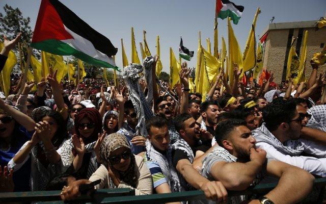 Les étudiants palestiniens qui soutiennent le mouvement du Fatah agitent le drapeau national et celui du mouvement durant un rassemblement en vue d'une campagne électorale pour le conseil étudiant à la  Birzeit University, à proximité de la ville cisjordanienne de Ramallah le 26 avril 2016 (Crédit :  / AFP PHOTO / ABBAS MOMANI