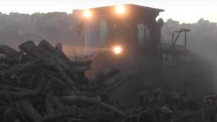 Un tracteur de l'Administration Civile confisque des piles de bois sur le site d'une usine de charbon en Cisjordanie, le 17 novembre 2016. (Crédit : Bureau de communication du COGAT )
