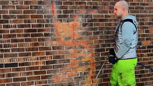 Corey Fleischer efface une croix gammée haute de 1 mètre 50 sur une maison de Montréal. (Crédit : courtesy)