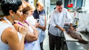 Des étudiantes observent le dépeçage d'un poisson lors de l'édition 2014 d'Open Restaurants. (Crédit : Tomer Foltyn)