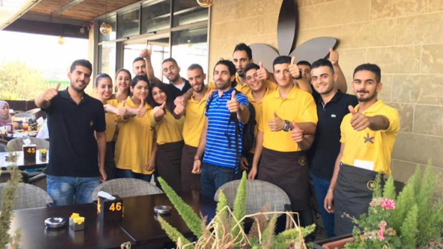 Le propriétaire John Saadeh, au centre, posant avec les membres de son personnel à l'extérieur du Jasmine Cafe à Naplouse (Crédit : Facebook)