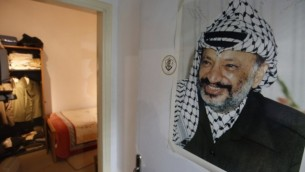 Photo prise le 9 novembre 2016 qui montre un tableau grand format de l'ancien dirigeant palestinien Yasser Arafat accroché à la porte d'une reconstitution de l'endroit dans lequel il a passé ses dernières années, au nouveau Arafat Museum à Ramallah, en Cisjordanie. (Crédits : AFP/Abbas Momani)