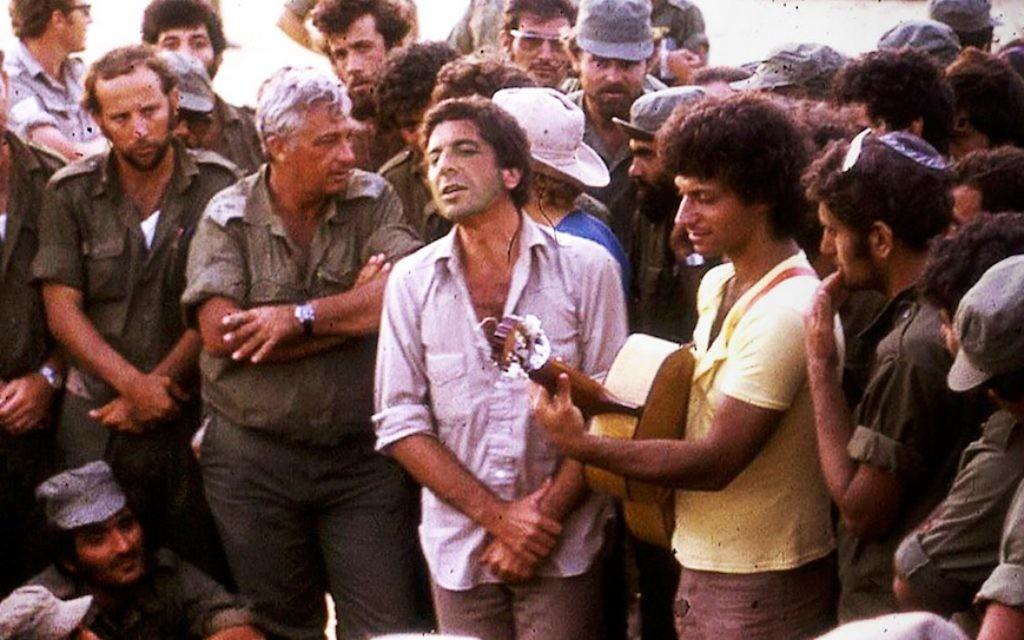 Au centre, Leonard Cohen chante avec le chanteur israélien Matti Caspi  la guitare, pour Ariel Sharon, avec les bras croisés, et le reste des troupes israéliennes, dans le Sinaï en 1973. (Crédit : Maariv via JTA)