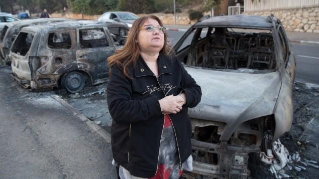 Une femme passe devant les voitures brûlées par les feux de forêt du 25 novembre 2016. (Crédits : AFP PHOTO / MENAHEM KAHANA)