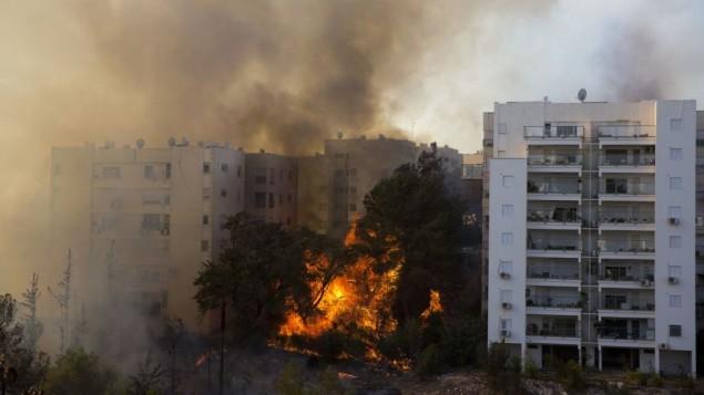 Photo prise le 24 novembre 2016. On y voit un feu de forêt ravageant la ville portuaire de Haïfa. De nombreuses personnes ont été évacuées, mais selon des responsables, certaines personnes sont bloquées à l'intérieur. Les pompiers luttent contre ces incendies. (Crédits : AFP PHOTO / Jack GUEZ))