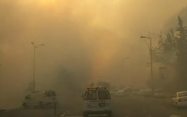 Une ambulance se frayant son chemin à travers les rues enfumées de Haïfa, le 24 novembre 2016. (Crédit : capture d'écran Dixième chaîne)