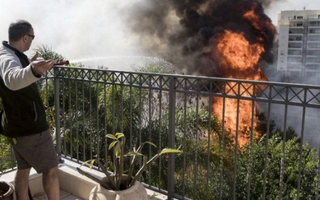 Un Israélien essaie d'éteindre un incendie d'un toit dans la ville d'Haïfa, le 24 novembre 2016 (Crédit : AFP PHOTO / JACK GUEZ)