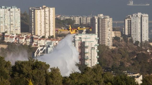 Un avion bombardier d'eau aide à éteindre les flammes qui ravagent Haïfa, le 25 novembre 2016. (Crédit : AFP/Menahem Kahana)