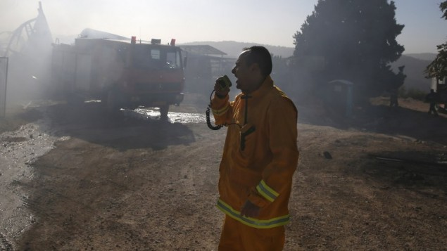 Un pompier israélien communique via talkie walkie pendant qu'ils tentent d'éteindre le feu à Beth Meir, le 25 novembre 2016. (Crédits : AFP PHOTO / AHMAD GHARABLI)