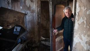L'israélien Aitan Shariel inspecte les dégâts sur sa maison, le 25 novembre 2016, après les feux terroristes, qui ont dévasté Haïfa. Crédits :  AFP PHOTO / MENAHEM KAHANA)