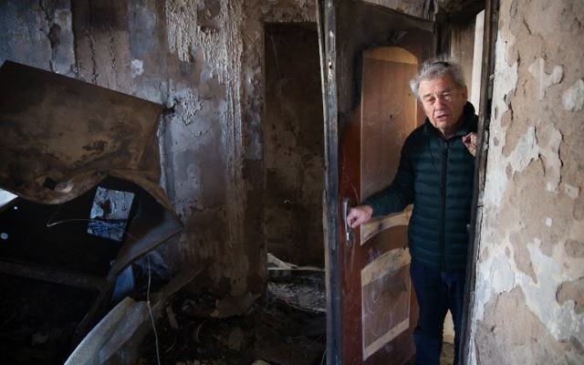 Aitan Shariel, habitant de Haïfa, inspecte les dégâts sur sa maison, le 25 novembre 2016, après les terribles incendies qui ont dévasté Haïfa. (Crédit :  AFP/Menahem Kahana)