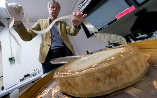 NikolausWostry, directeur des collections de la Filmarchiv Austria, montre un ancien film endommagé, à Laxenburg, le 15 novembre 2016. (Crédit : Joe Klamar/AFP)