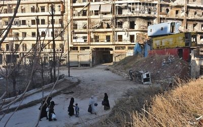 Des Syriens fuyant les violences dans les quartiers est d'Alep, tenus par les rebelles, passent devant une barricade improvisée de carcasses de bus dans le quartier Bal al-Hadid, saisi par les forces du régime gouvernemental, le 7 décembre 2016. (Crédit : George Ourfalian/AFP)