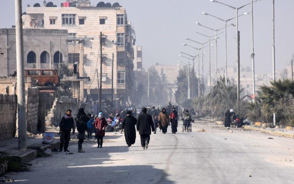 Les civils syriens marchant vers un poste de contrôle tenu par les forces pro-gouvernementales, au rond-point de la rue Al-Hawoz, après avoir quitté les quartiers de l'est d'Alep le 10 décembre 2016 (Crédit : George Ourfalian/AFP)