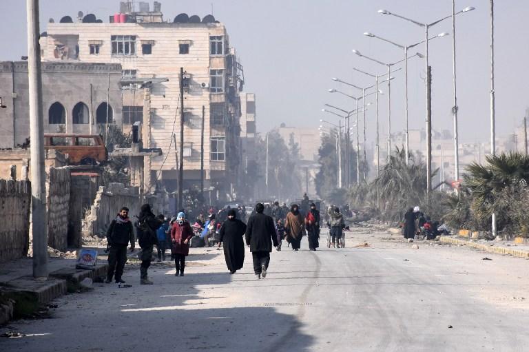 Les civils syriens marchant vers un poste de contrôle tenu par les forces pro-gouvernementales, au rond-point de la rue Al-Hawoz, après avoir quitté les quartiers de l'est d'Alep le 10 décembre 2016 (Crédit : AFP PHOTO / George OURFALIAN)