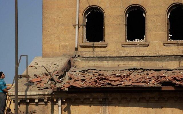 Un Egyptien sur la scène d'une explosion qui a ciblé l'église orthodoxe copte Saint Pierre et  Saint Paul du Caire et a fait 26 morts, le 11 décembre 2016. (Crédit :  Suhail Saleh/AFP)