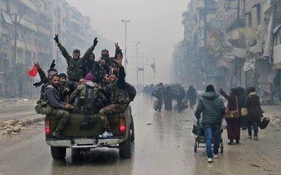 Des combattants pro-régime syrien et des habitants fuyant les violences dans le quartier Bustan al-Qasr d'Alep, le 13 décembre 2016. (Crédit : AFP/Stringer)