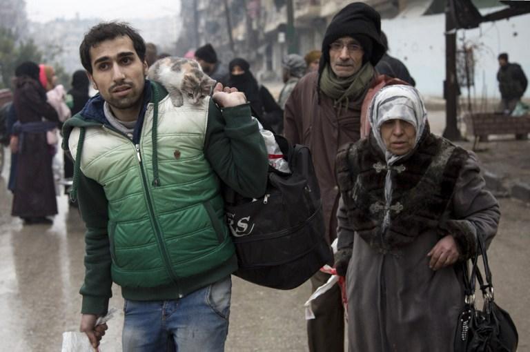 Des Syriens quittent un quartier d'Alep tenu par les rebelles pour la partie sous contrôle gouvernementale pendant une opération des forces du gouvernement syrien pour reprendre la ville assiégée, le 13 décembre 2016. (Crédit : Karam al-Masri/AFP)