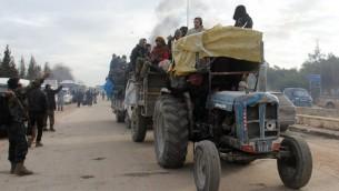 Un tracteur évacue des Syriens des zones assiégées d'Alep, le 16 décembre 2016. (Crédit : Omar Haj Kadour/AFP)
