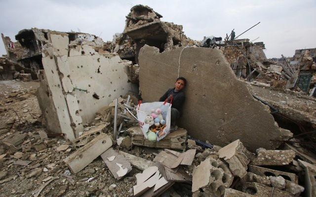Un petit garçon syrien est assis avec les objets qu'il a récupéré des ruines de sa maison, dans le quartier Al-Arkoub d'Alep, après une opération des forces pro-régime pour reprendre la ville au rebelles, le 17 décembre 2016. (Crédit : Youssef Karwashan/AFP)