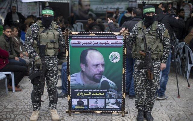 Des membres des Brigades Ezzedine al-Qassam Brigades, la branche armée du Hamas, avec un portrait de Mohammed al-Zoari, qui a été tué en Tunisie, pendant une cérémonie en son honneur dans la ville de Gaza, le 18 décembre 2016. (Crédit : Mahmud Hams/AFP)