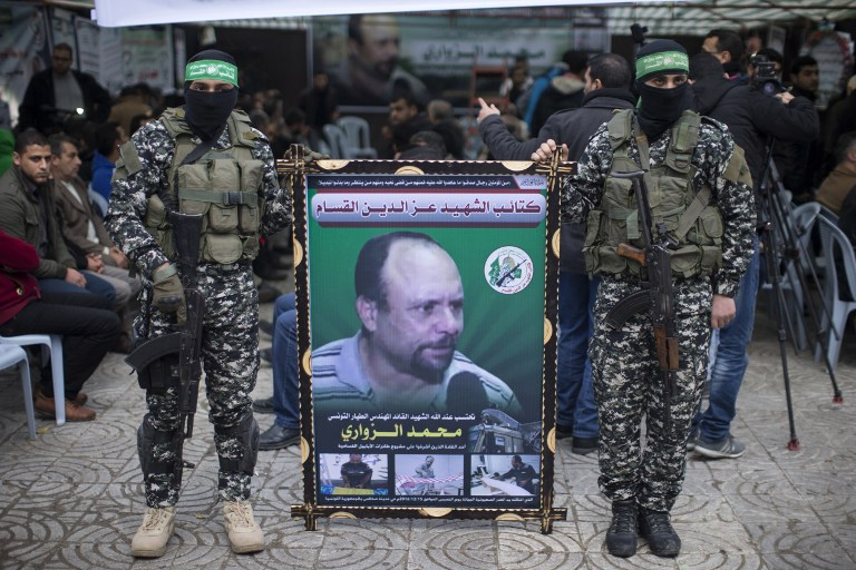 Des membres des Brigades Ezzedine al-Qassam Brigades, la branche armée du Hamas, avec un portrait de Mohamed Zoari, qui a été tué en Tunisie, pendant une cérémonie en son honneur dans la ville de Gaza, le 18 décembre 2016. (Crédot : Mahmud Hams/AFP)