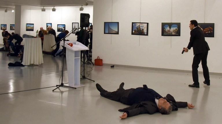 Andreï Karlov, l'ambassadeur de la Russie auprès de la Turquie, gît au sol près de son assassin, qui vise toujours le public d'une exposition à Ankara, le 19 décembre 2016. (Crédit : STRINGER/AFP)