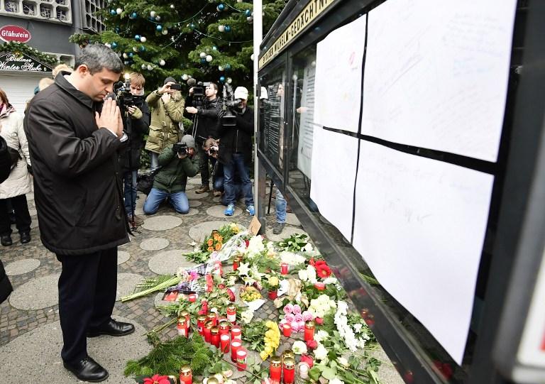 Raed Saleh, le président du groupe social démocrate du SPD au Parlement allemand, prie devant l'église du Souvenir de Berlin, au lendemain d'une attaque au camion bélier contre le marché de Noël de la ville qui a fait au moins 12 morts, le 20 décembre 2016. (Crédit : Tobias Shwarz/AFP)