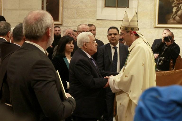 Le président de l'Autorité palestinienne Mahmoud Abbas, au centre à gauche, avec l'archevêque Pierbattista Pizzaballa, l'administrateur apostolique du Patriarche latin de Jérusalem, pendant la messe de Noël de l'église Sainte-Catherine de l'église de la Nativité, à Bethléem, en Cisjordanie, le 25 décembre 2016. (Crédit : Musa al-Shaer/Pool/AFP)