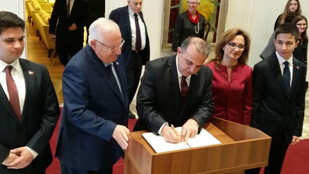 Le président Reuven Rivlin, à gauche, et le nouvel ambassadeur de la Turquie en Israël, Kemal Okem, qui signe le livre d'or de la résidence présidentielle, à Jérusalem, le 12 décembre 2016. (Crédit : Raphael Ahren/Times of Israël)