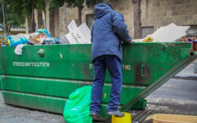 Photo d'illustration d'un homme cherchant de la nourriture dans une poubelle (Crédit : Flash 90)