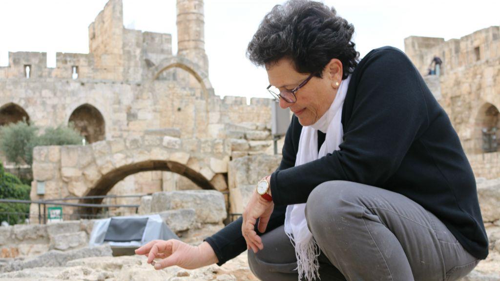 L'archéologue Orna Cohen avec l'ancienne pièce de monnaie trouvée dans la cour de la Tour de David (Crédit : Autorisation Shay Amiran)