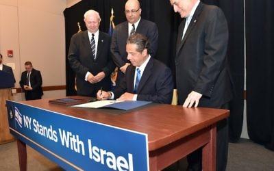 Le gouverneur Andrew M. Cuomo signe un ordre exécutif qui impose le désinvestissement des fonds publiques des entreprises qui soutiennent l mouvement BDS, au Harvard Club de New York City, le 5 juin 2016. (Crédit : Kevin P. Coughlin/Office of Governor Andrew M. Cuomo)