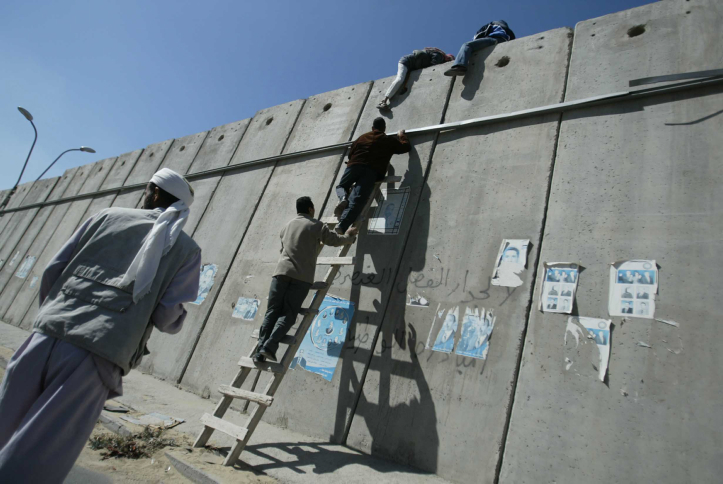 Des fidèles palestiniens grimpent sur une section de la barrière de séparation d'Israël avec le village  A-Ram vers Jérusalem, alors qu'ils vont prier à la mosquée Al-Aqsa, le 20 octobre 2016. (Crédit : Pierre Terdjman/Flash90)