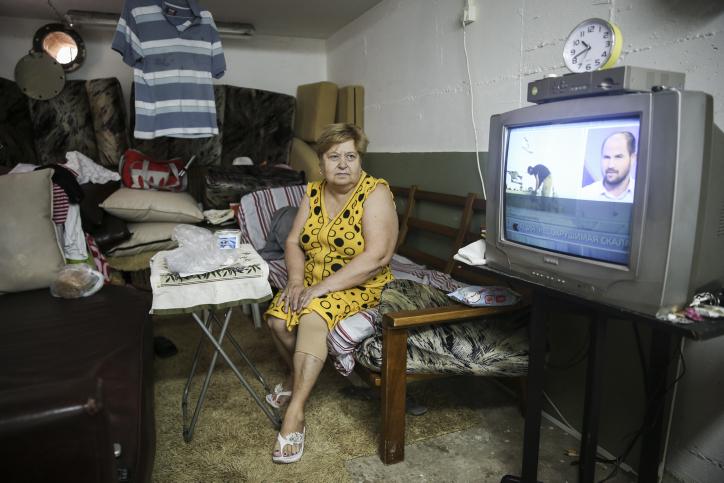 Olga, immigrante de l'ancienne Union soviétique, regarde les informations dans l'abri anti-bombe qu'elle a transformé en maison temporaire, à Ashkelon, le 30 juillet 2014. (Crédit : Hadas Parush/Flash90)